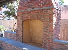 Rumford style fireplace was built out of Robinson Cambridge brick and roofing tiles with Eldorado capping stones.